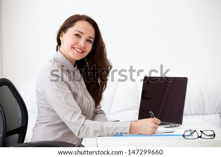 Portrait of businesswoman with laptop writes on a document at office