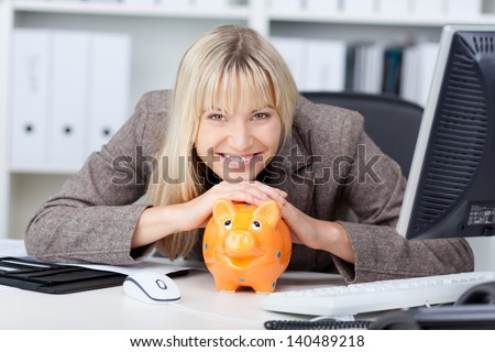 Portrait of businesswoman with piggy bank at desk in office - stock photo