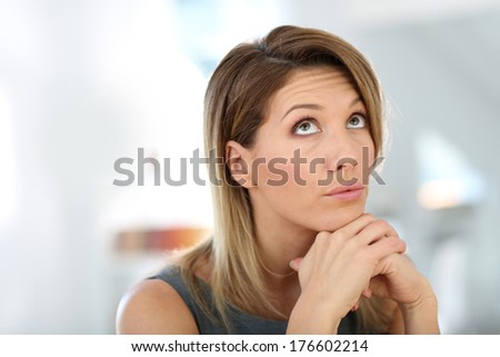 Portrait of businesswoman with thoughtful look - stock photo