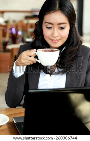portrait of businesswoman working on her laptop while taking a coffee break - stock photo