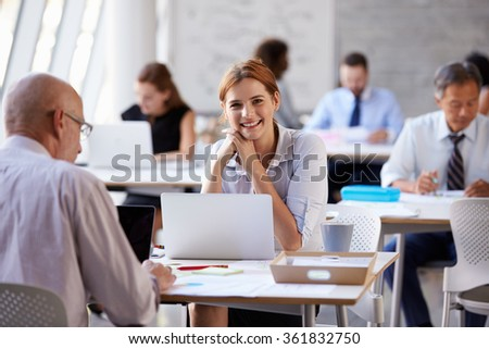 Portrait Of Businesswoman Working On Laptop In Busy Office - stock photo