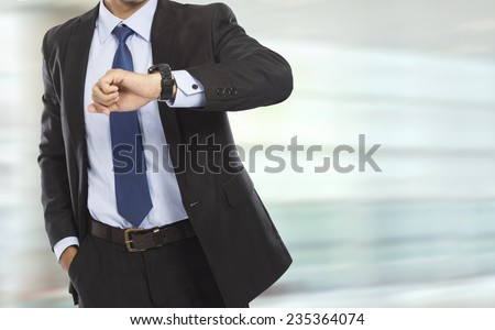 portrait of busy business man body looking at his watch in rush hour - stock photo