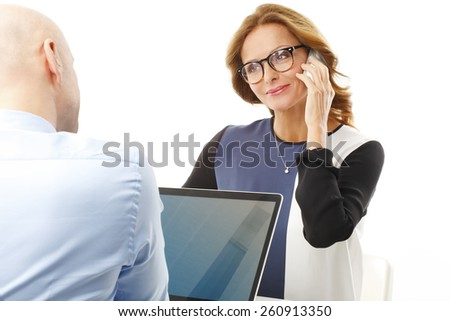 Portrait of busy business woman making a call while businessman working at laptop. Isolated on white background.  - stock photo
