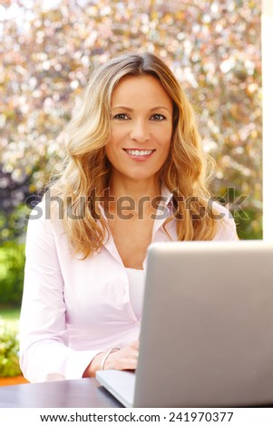 Portrait of busy business woman typing at laptop while sitting at home at garden.
