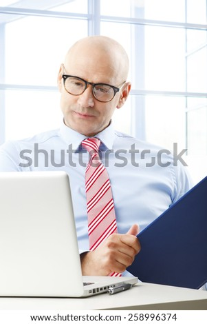 Portrait of busy businessman sitting at office in front of computer while holding file in his hand.  - stock photo
