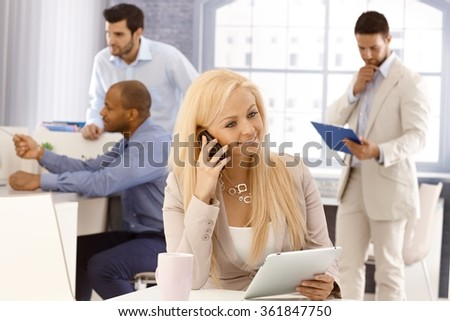 Portrait of busy businesswoman sitting at desk, talking on mobilephone, using tablet computer, smiling. - stock photo