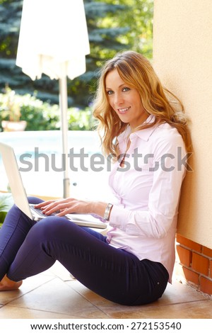 Portrait of busy businesswoman sitting at garden while using her laptop and writing financial report. Business person.  - stock photo