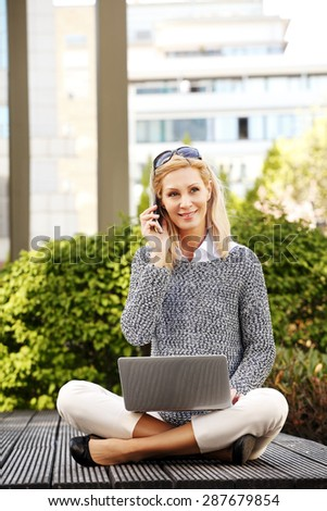 Portrait of busy businesswoman sitting at park and working online with laptop while making call on her mobile phone. Casual woman sitting with turkish seat and smiling to the camera.