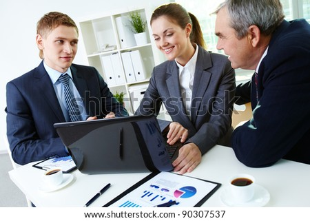 Portrait of busy people discussing new project at meeting in office
