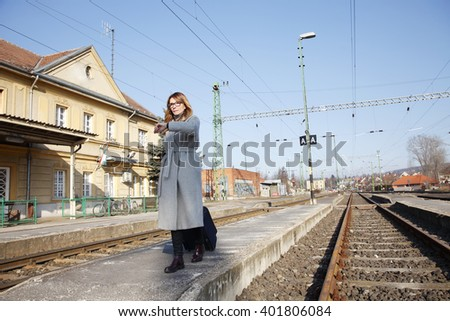 Portrait of busy professional woman walking on railway platform and checking the time on her watch. - stock photo