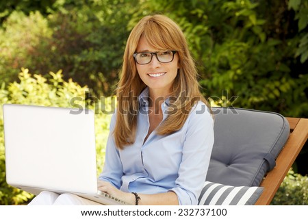 Portrait of busy sales woman working on laptop while sitting at home in garden.