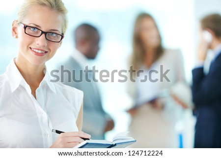 Portrait of busy secretary looking at camera - stock photo