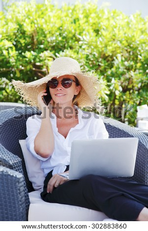 Portrait of busy woman at home. Professional female sitting at garden and making call while using her laptop and working online.