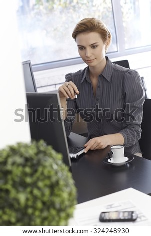 Portrait of busy working businesswoman, sitting at desk in bright office, using computer. - stock photo
