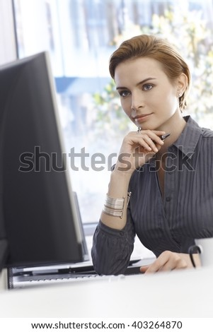 Portrait of busy working businesswoman, sitting at desk, using computer. - stock photo