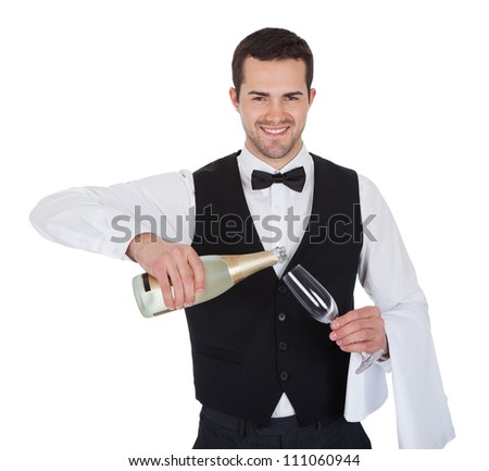 Portrait of butler pouring champagne into glass. Isolated on white - stock photo