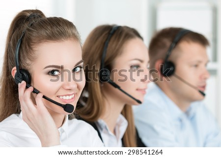 Portrait of call center worker accompanied by her team. Smiling customer support operator at work. Help and support concept - stock photo