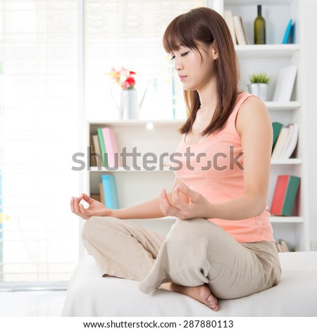 Portrait of calm Asian girl meditation in the morning. Young woman indoors living lifestyle at home.