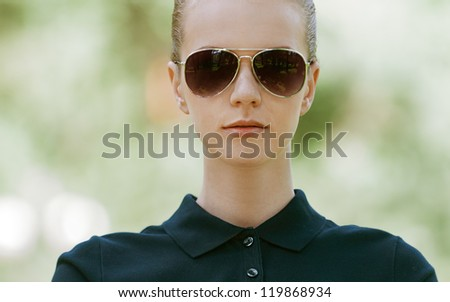 Portrait of calm beautiful young woman in sunglasses, against green of summer park. - stock photo