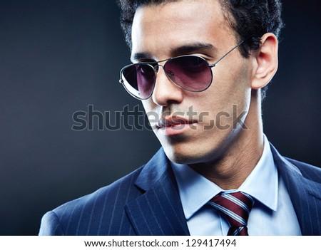 Portrait of calm man in sunglasses posing for camera - stock photo