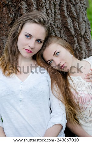 Portrait of calm pretty girl friends leaning against big tree on outdoors background - stock photo