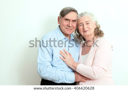 Portrait of candid senior couple enjoying their retirement. Affectionate elderly couple with beautiful beaming friendly smiles posing together in  close embrace on white background - stock photo