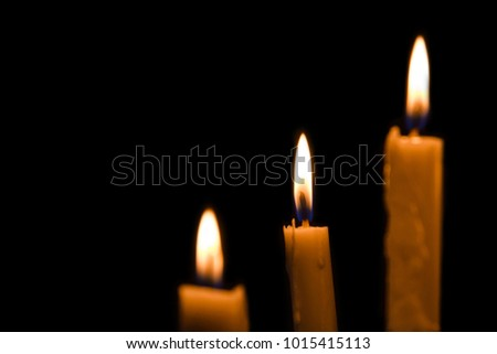 portrait of candles burning brightly on black backgorund with copy space
