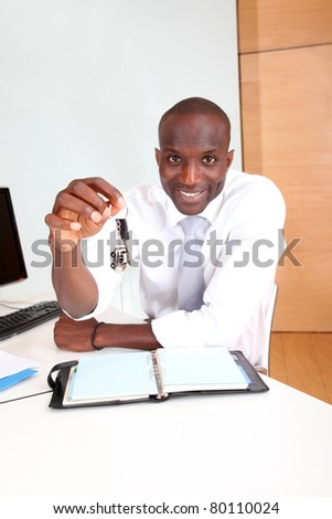 Portrait of car seller holding car keys - stock photo