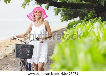 portrait of carefree woman having fun and walking with bicycle on the beach - stock photo