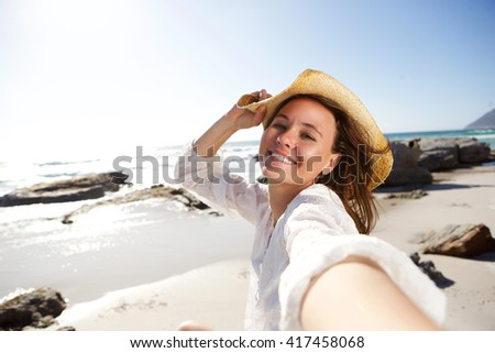 Portrait of carefree young lady on holiday at the beach taking selfie  - stock photo