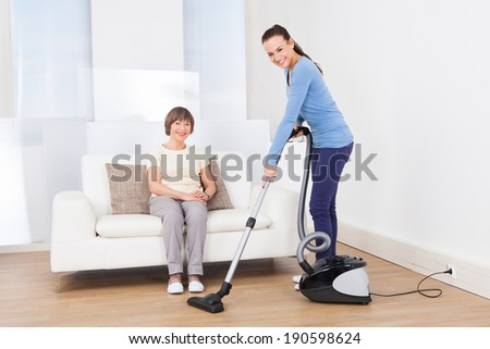 Portrait of caretaker cleaning floor with vacuum cleaner while senior woman sitting on sofa at nursing home - stock photo