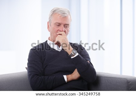 Portrait of careworn senior man sitting at home on sofa.