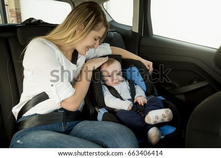 Portrait of caring mother with baby boy on car back seat