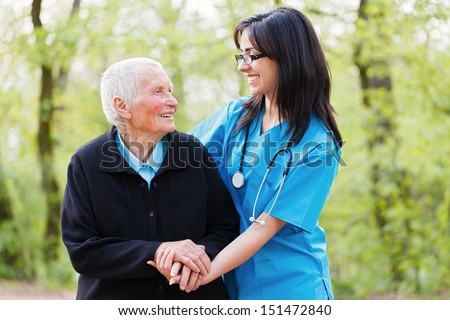 Portrait of caring nurse and happy senior lady while  holding hands. - stock photo