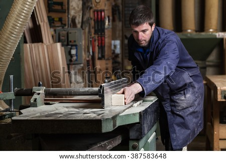 Portrait of Carpenter man cutting wood with table saw in workshop - stock photo