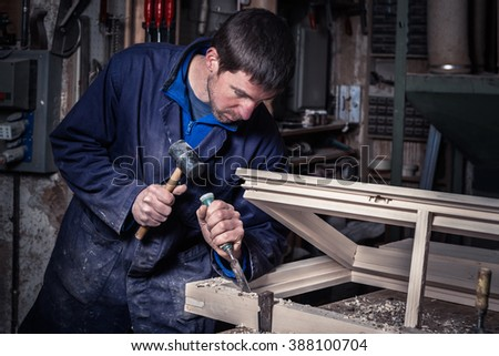 Portrait of Carpenter using Hammer and Chisel on a Wooden Window in his Workshop