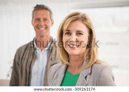 Portrait of casual business colleagues smiling at camera in the office - stock photo