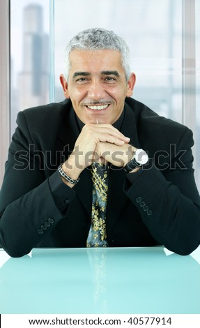 Portrait of casual businessman, sitting at desk in front of office windows, leaning on hands, smiling.