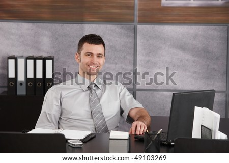 Portrait of casual businessman sitting at desk wearing short sleeved shirt, smiling. Copyspace on right. - stock photo