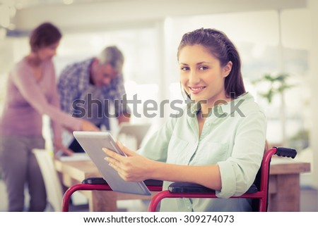 Portrait of casual businesswoman in wheelchair using tablet in the office