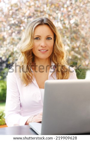 Portrait of casual businesswoman using computer while sitting at home in garden. Small business.
