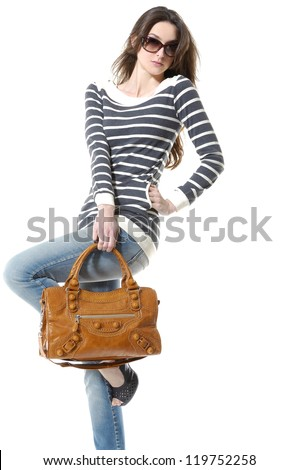 portrait of casual fashion woman with bag posing in studio - stock photo