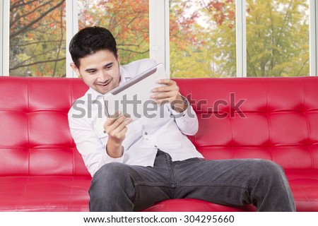 Portrait of casual man sitting on sofa while using a digital tablet to play game - stock photo