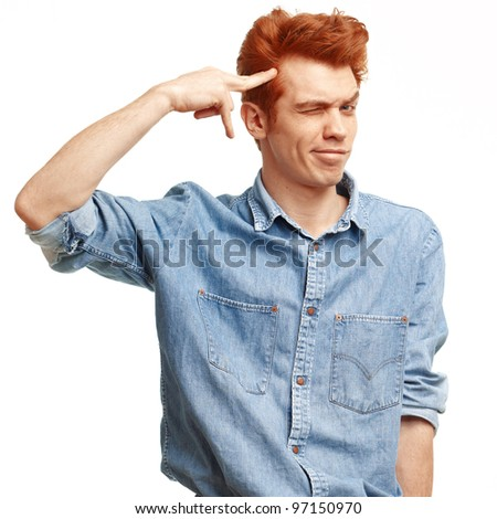Portrait of casual red haired young man with imaginary gun standing over white background. - stock photo