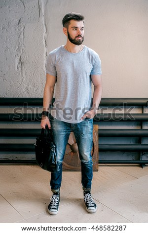 Portrait of casual stylish bearded man looking away with handbag and hand in pocket.Old background.