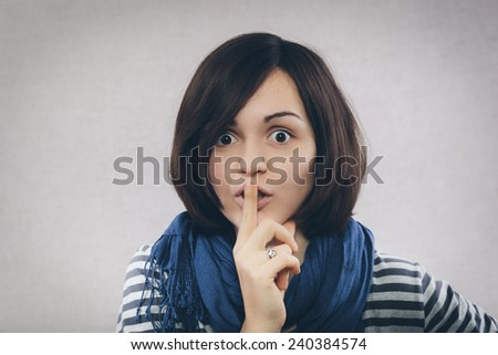 Portrait of casual woman with finger on lips - stock photo