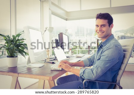 Portrait of casual young businessman using computer in office - stock photo
