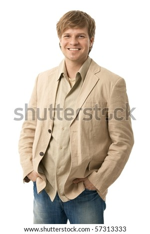 Portrait of casual young man, standing with hands in pocket, smiling. Isolated on white.? - stock photo