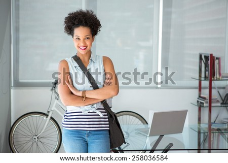 Portrait of casual young woman standing with arms crossed - stock photo