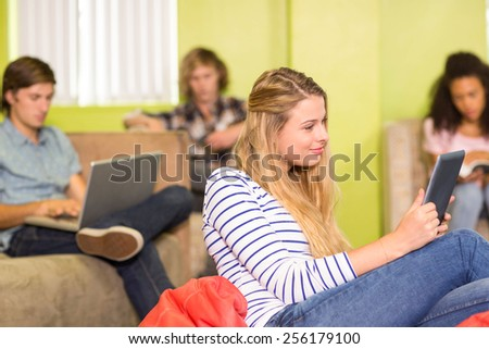 Portrait of casual young woman using digital tablet in office - stock photo